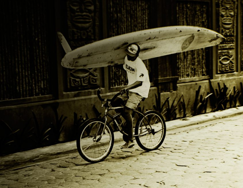 Belize surfer on a bike