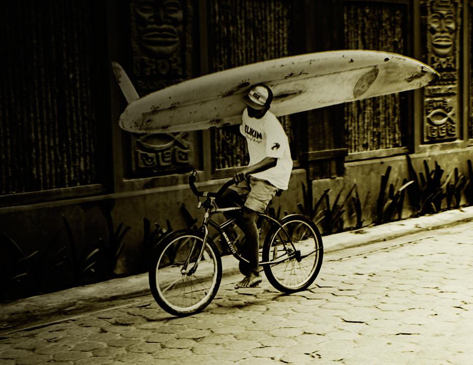 Belize surfer on a bike
