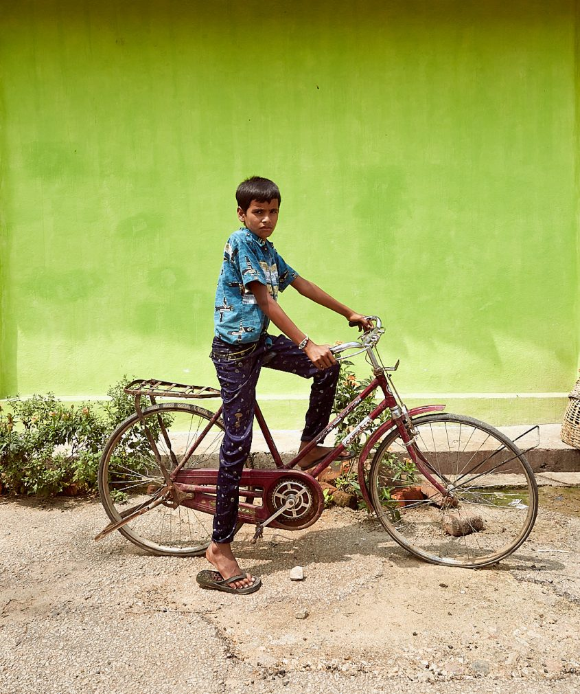 Boy on bike against green wall